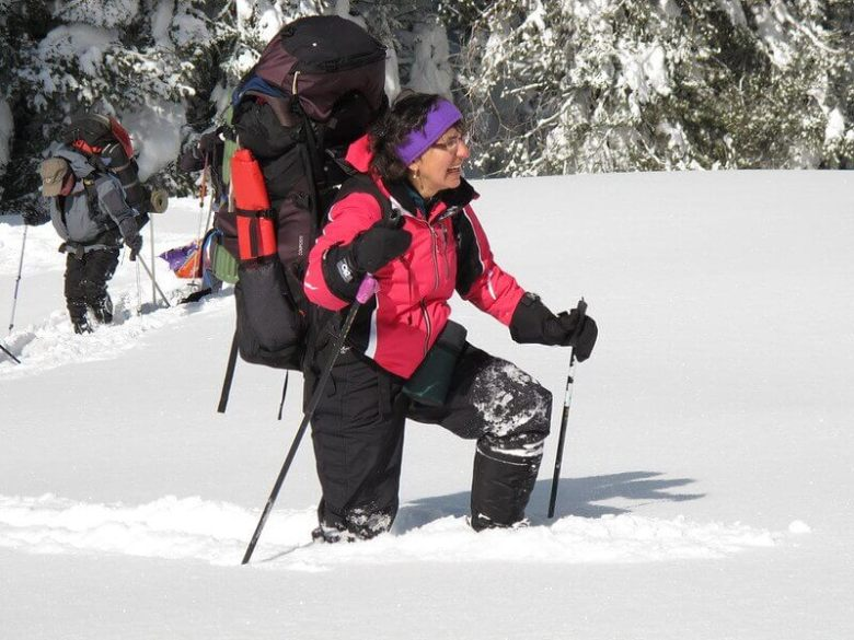Woman wading through knee deep snow with backpack on. How to take a winter camping trip.