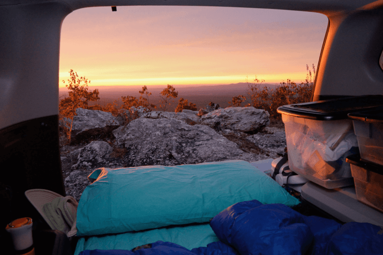 sunrise view beyond a cliff with tent camping essentials in the foreground