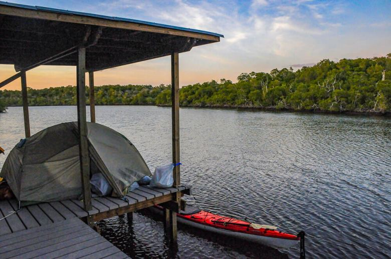 A tent on a platform with a kayak in the water next to it.