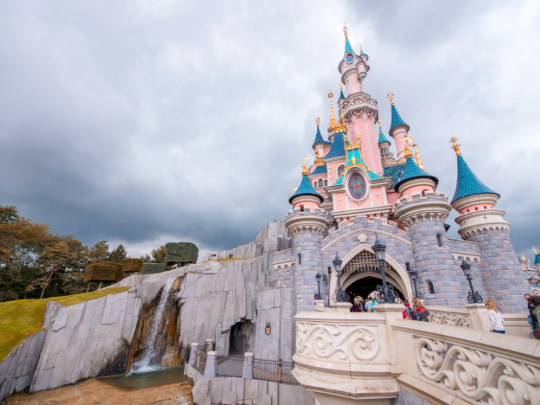The Disney Castle with a small waterfall on a cloudy day