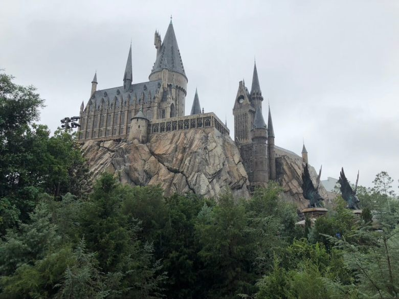 Hogwarts Castle up on a rock with trees down below. Harry Potter World Guide.