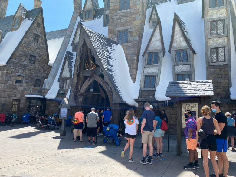 Line to enter the restaurant, the Three Broomsticks with a peaked roof and fake snow on top.