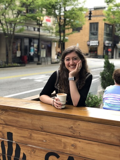 Woman sitting at wooden table with coffee at one of the best coffee shops in Winston-Salem.