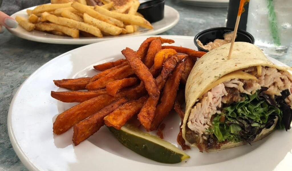 Turkey wrap with sweet potato fries and another plate of food in the background