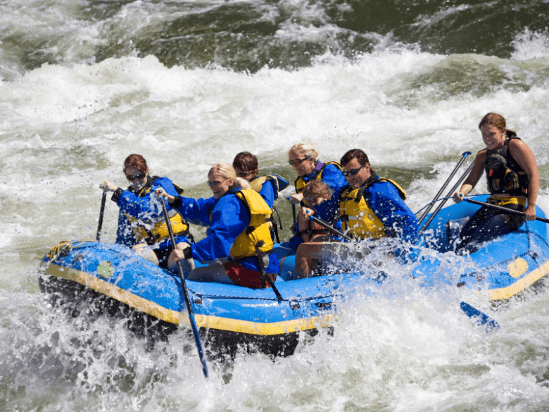 Group in a blue raft in white water. What to wear white water rafting.