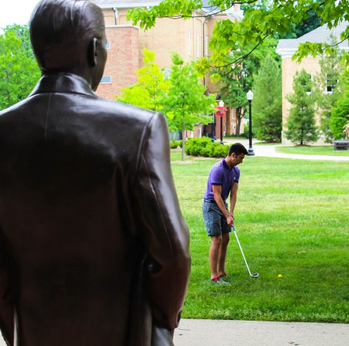 Alex Miller sizing up his lie under the watchful eyes of Ronald Reagan.