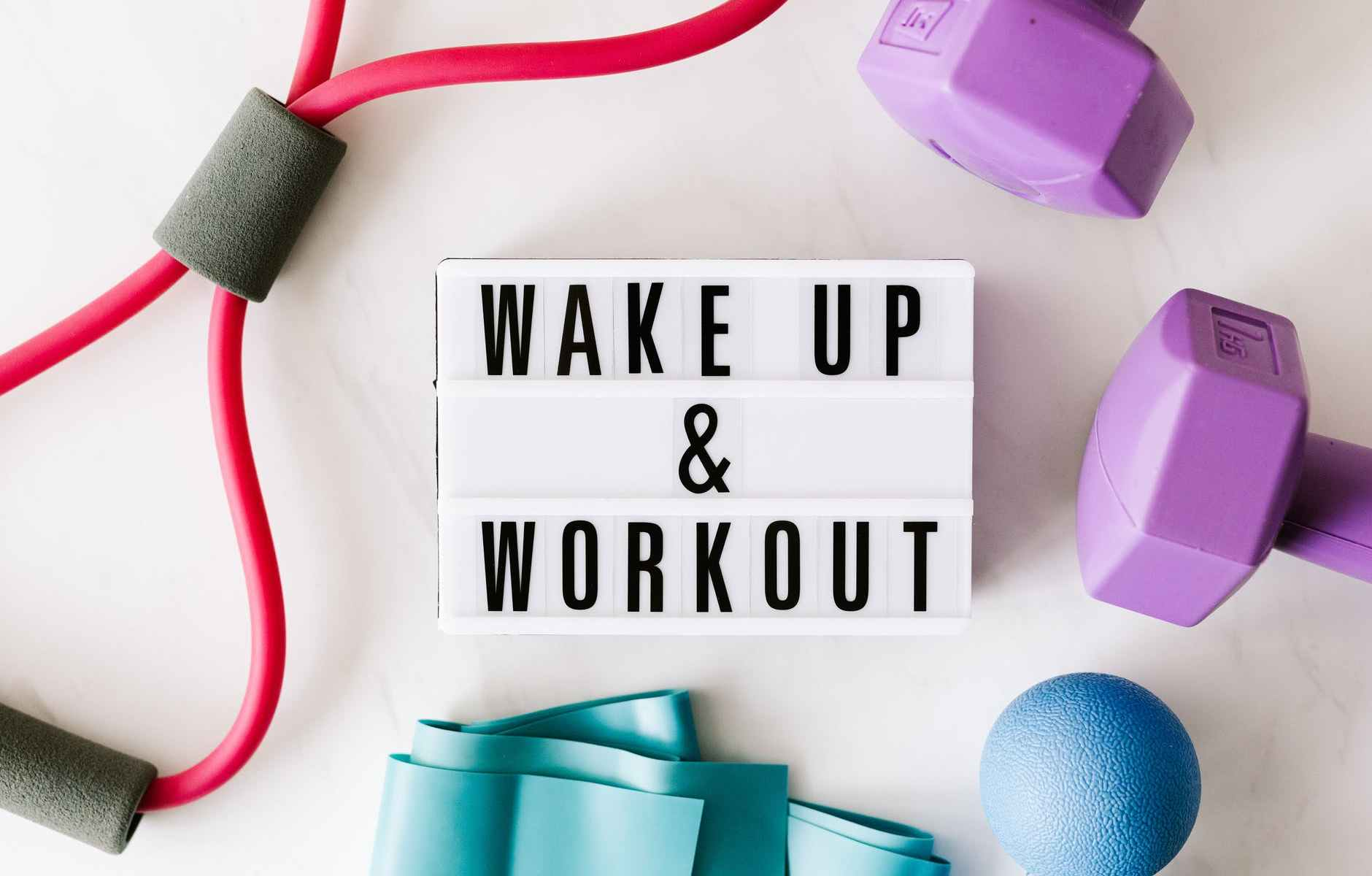 wake up and workout title on light box surface surrounded by colorful sport equipment