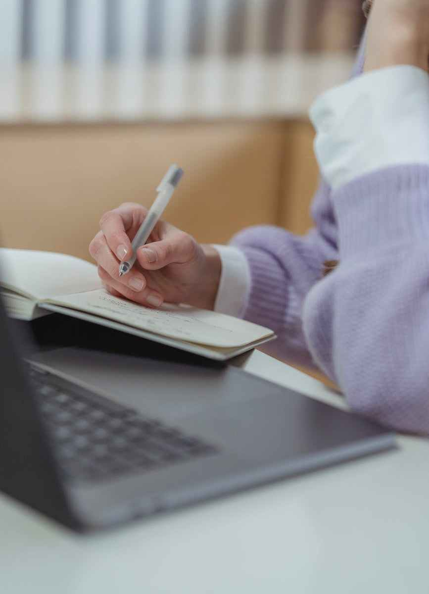 woman taking notes in notebook while using laptop