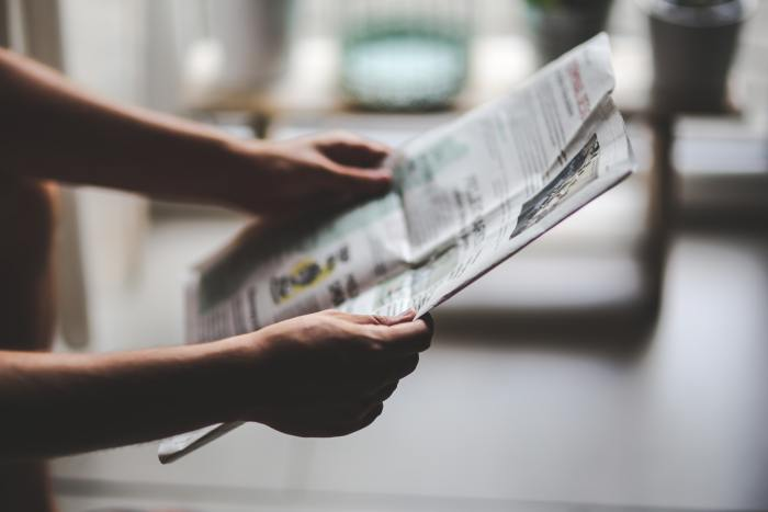 A person holding a newspaper