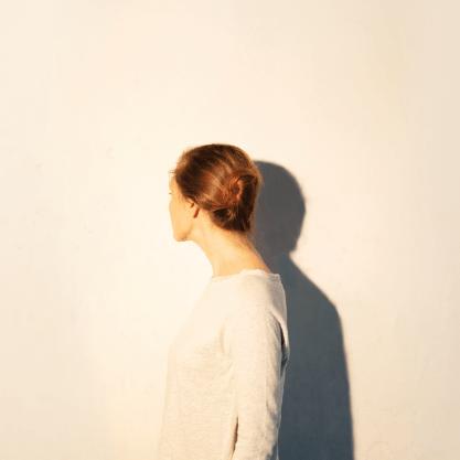 femme_cie_traversée_spectacle_fond_clair_lumière_centrale_femme_de_dos_cheveux_blond_pull_biege2
