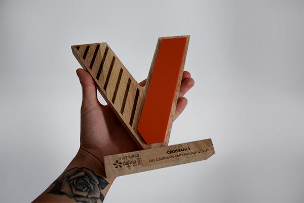 trophée en bois sur mesure, bicolore, orange et bois, forme en V, trophée victoire, porté dans une main, gravure du logo et d'écritures, studio l'ingrédient