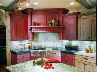 Farmhouse kitchen with exposed beams in the ceiling red painted cabinets and light wood cabinets granite countertops
