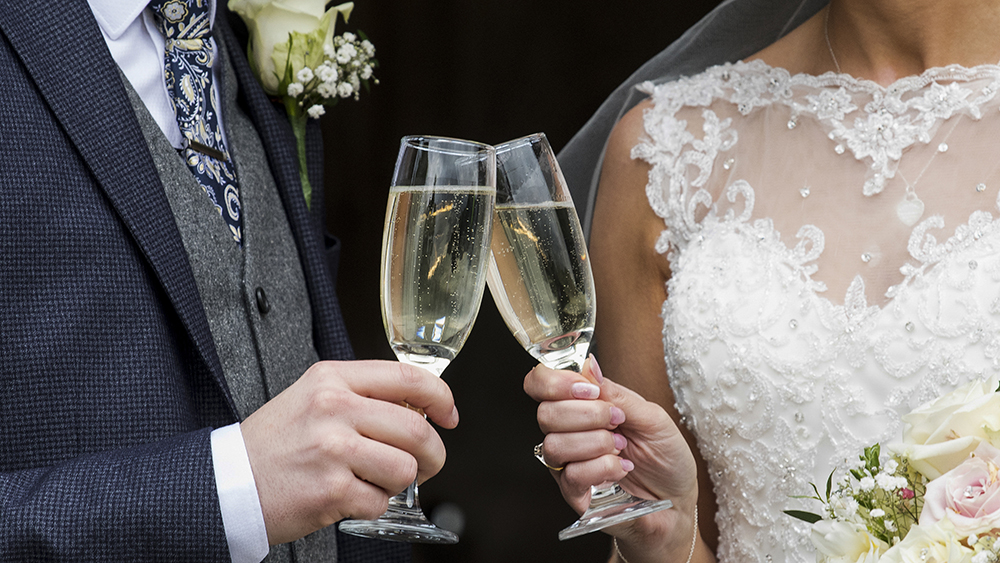 bride & groom heers clinking glasses together