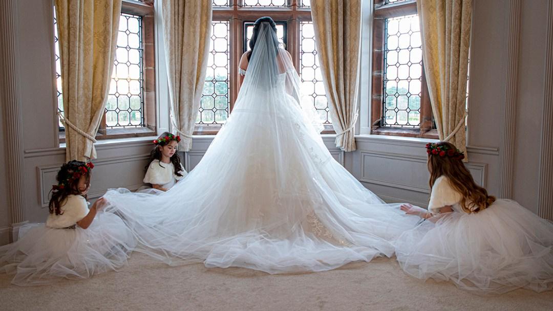 Flower girls adjust bride's dress