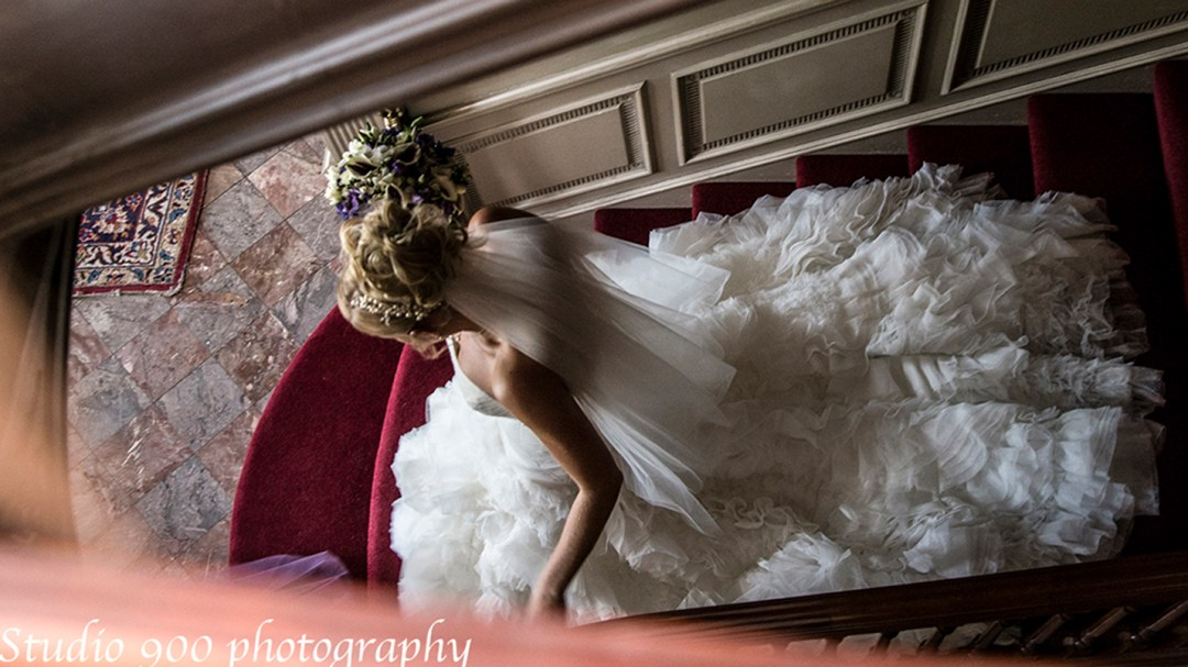 Bride walks down stairs with trailing dress