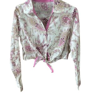 Long-sleeved, cropped, cream, cotton-blend button-up, collared shirt. The shirt has a pink trim around the collar and the fabric has a delicate pink paisley print. Top has a tie at the centre front hem which can be tied and adjusted. On a plain white background.