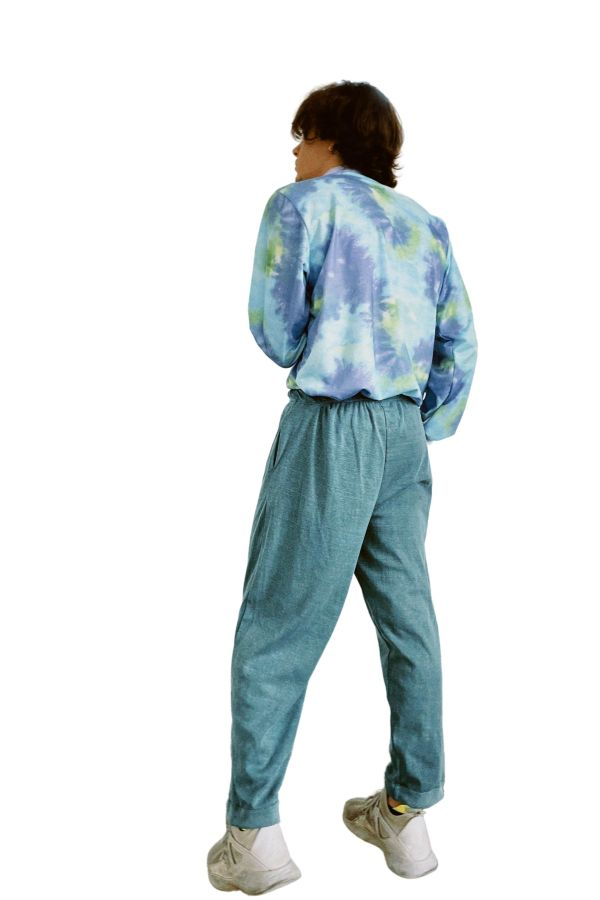 Masculine model with dark hair standing with his back turned, wearing the Candor Tie Dye For Top and Lluvia pants. The Tie Dye For Top has a vintage-style lilac rib high collar and is a lilac, light blue and green tie-dye fabric. The Lluvia pants are a light teal enzyme wash cotton blend vintage fabric, in a straight-leg masculine style, with rolled hem and adjustable drawstring waistband.