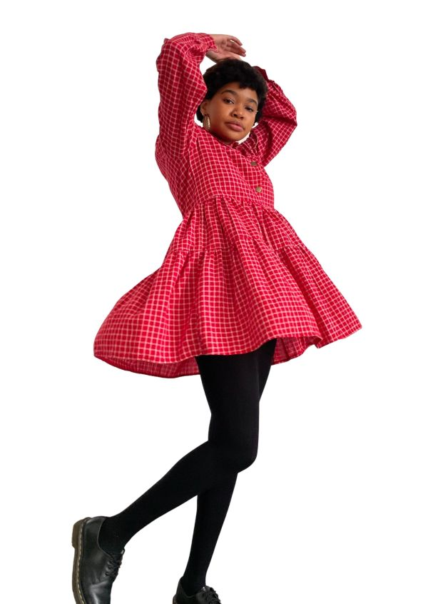 Feminine model standing mid-twirl, with her arms raised up, wearing the Candor Check It Out dress. The dress is a mini double layered frill dress, with long bell sleeves gathered into cuff with shell button, in a red and white checked fabric.