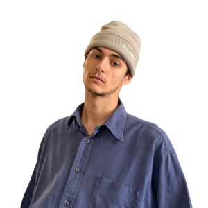 Male model standing against a plain white background, from the waist up. wearing the Tan Candor Beanie.