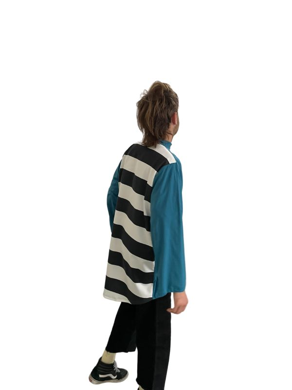 Masculine model standing with his back turned, wearing the Candor Striped Back Top. The shirt is blue with a black and white striped fabric back panel, has long sleeves, a high collar, scoop hem feature and classic Candor label at 7cm drop centre front.