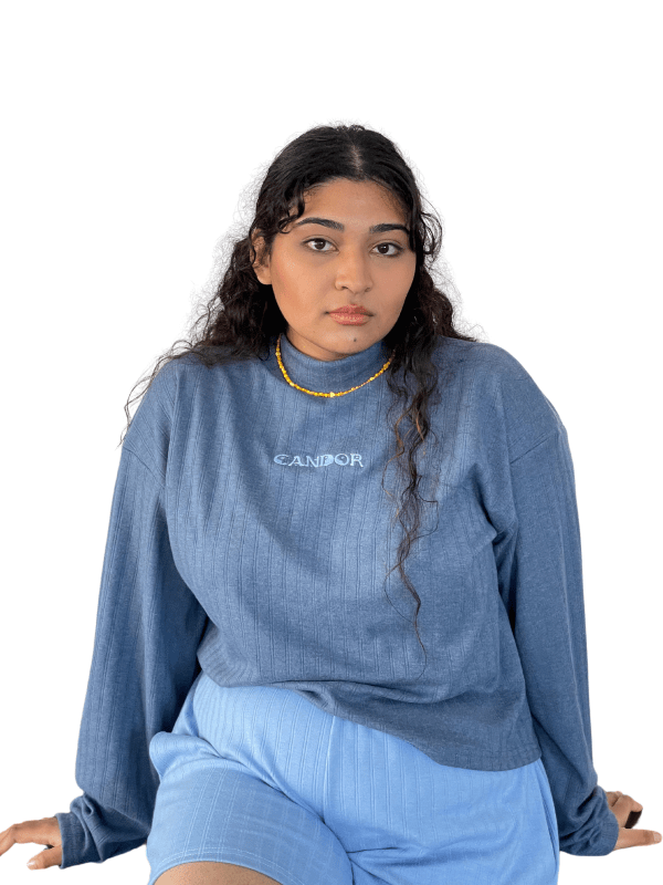 Feminine model of colour seated against a white backdrop with hands placed gently behind her on the ground. Model is wearing the Candor Pisces set. The top is a grey-blue long-sleeve with marrowed edges and baby blue signature Candor embroidery on the front centre.