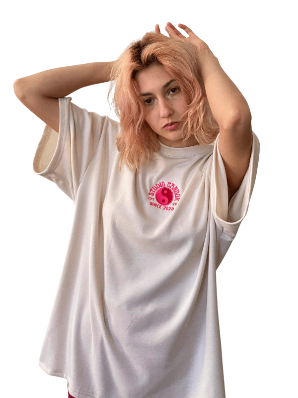 Caucasian feminine model stood with hands raised above her head, playing with her hair in the Candor Taurus Top. The top is oversized and cream with a hot pink and cream embroidery on the center front with a yin-yang sign.