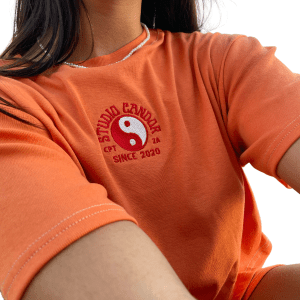 Zoomed in picture of the Candor Citrine top. Photo displays the bright orange hue of the top along with the red and white yin and yang embroidery featured on centre front.