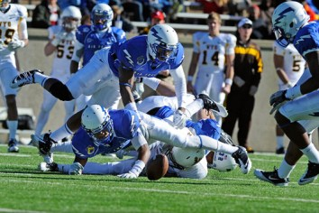 Falcons Jon Davis (top) and Anthony Wooding Jr. dive for the ball during the first quarter of the game against Wyoming, November 12, 2011 at Falcon Stadium, Colorado Springs, CO. (U.S. Air Force photo/Liz Copan)