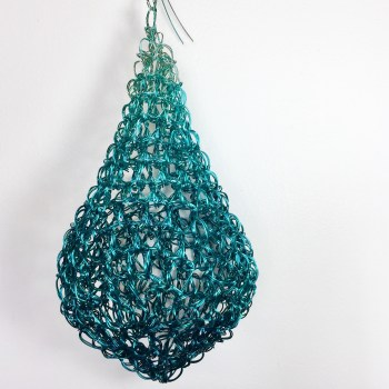 Hand crocheted water drop in deep turquoise blue slowly becomes a light turquoise green