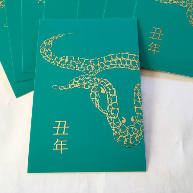 Japanese New Year postcards called nengajo for the 2021 Year of the Metal Ox in raised gold on a turquoise background.