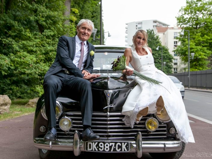 couple de mariés assis sur voiture de collection de mariage
