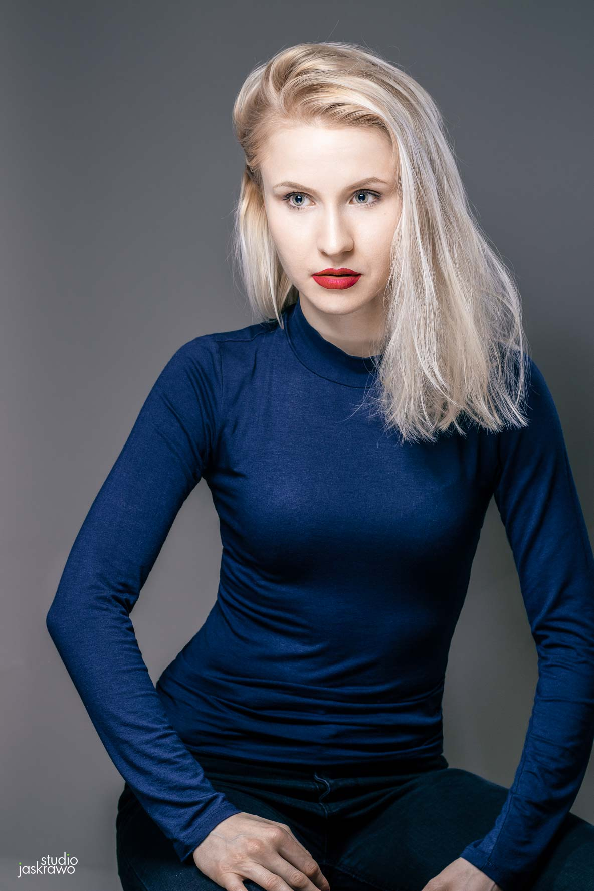 blondynka w niebieskiej bluzce z pomalowanymi czerwonymi ustami