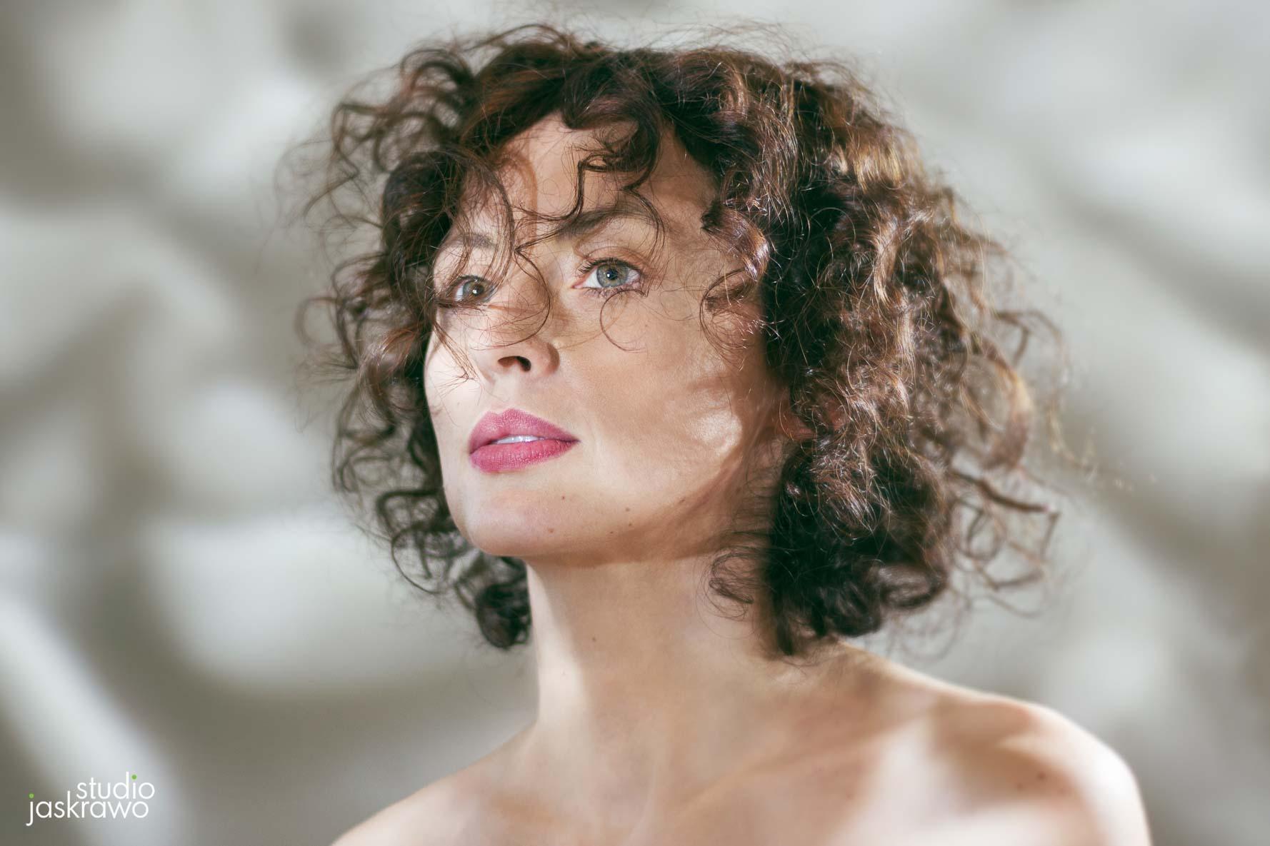 twarz kobiety z kręconymi włosami patrzącej w lewo