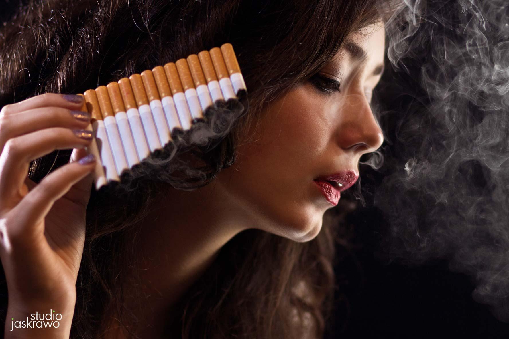 młoda kobieta trzyma kilka papierosów w jednej ręce