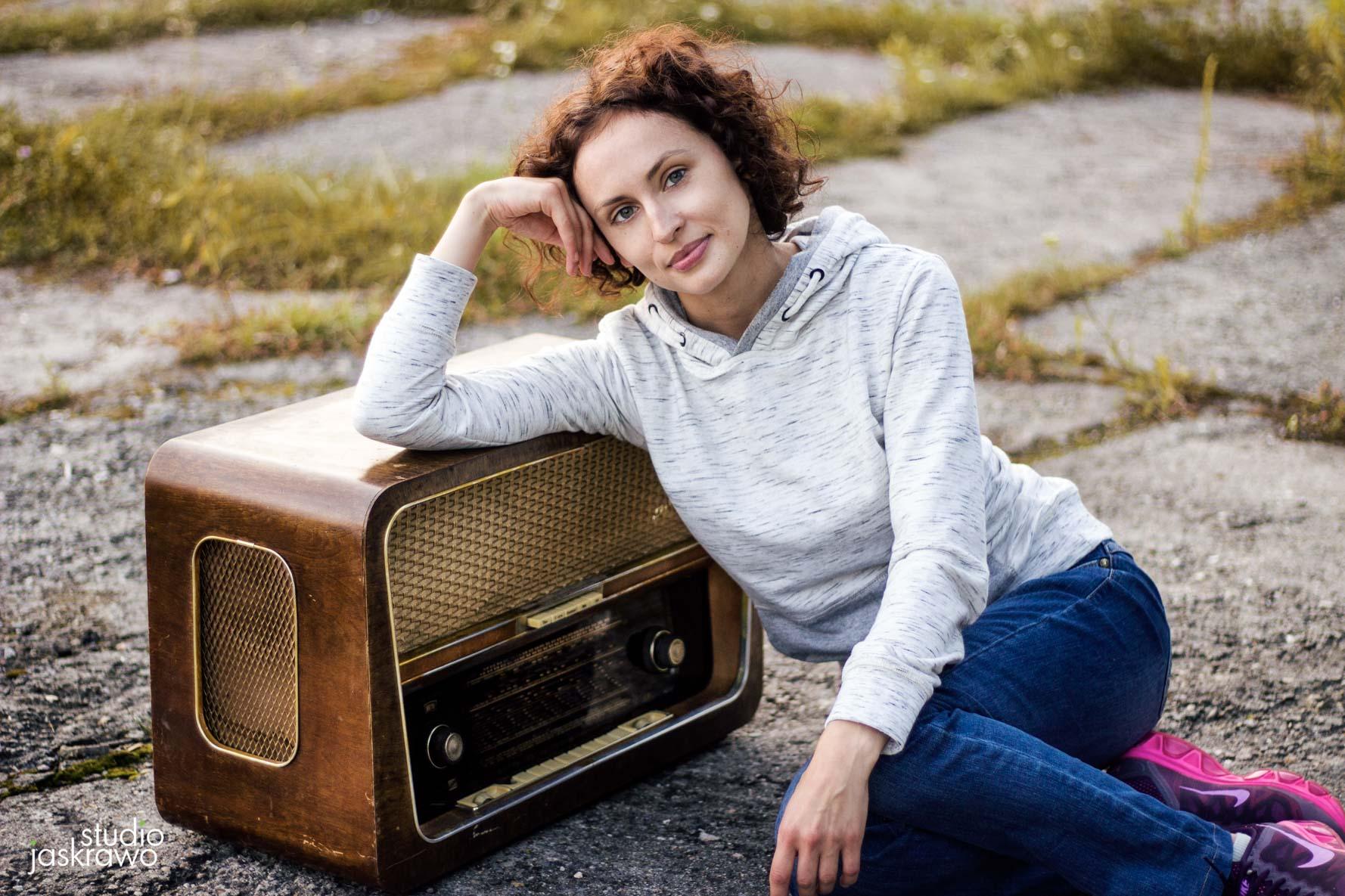 dziewczyna siedząca na ziemi opiera się o stare radio
