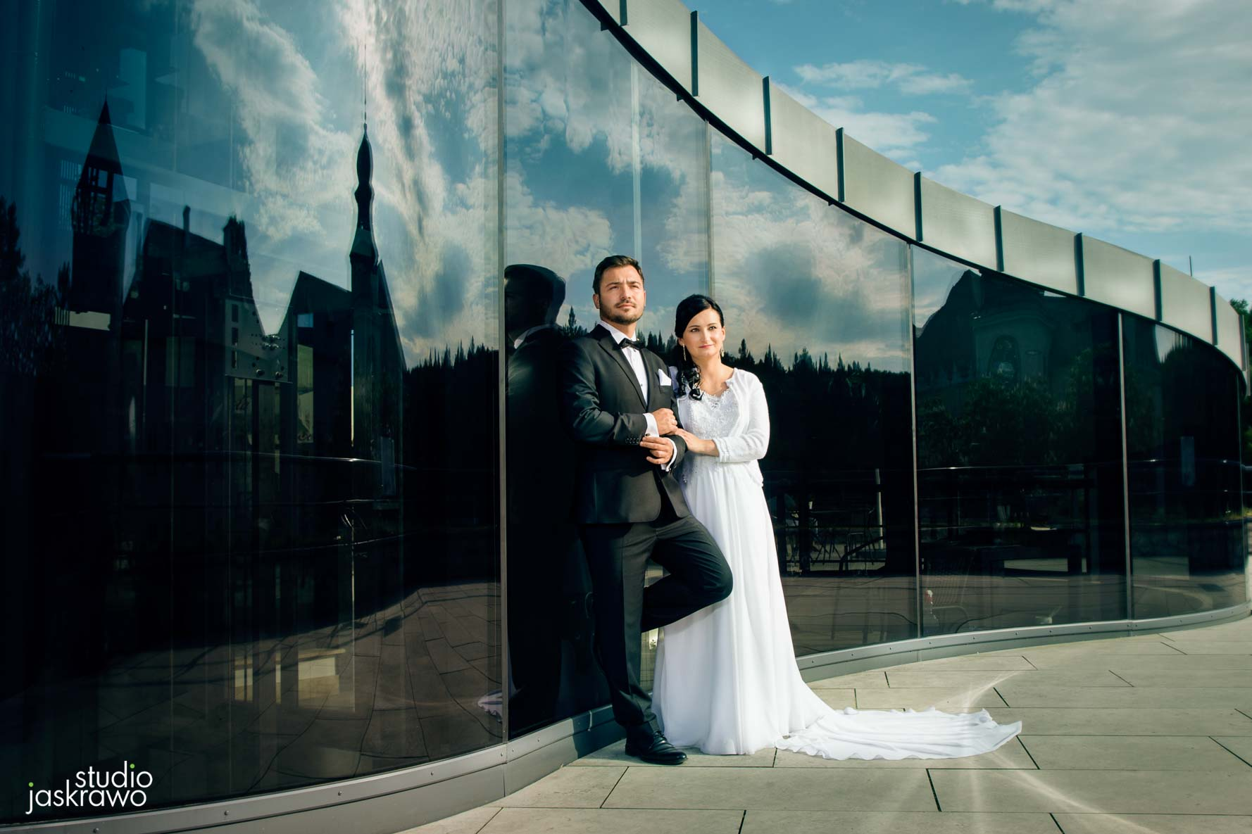kobieta w sukni ślubnej i mężczyzna w garniturze na tle szklanej ściany