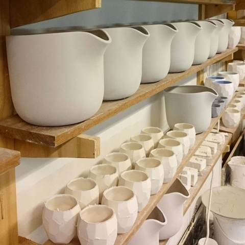 Flowerpots are drying on the shelf before these go into the kiln