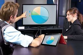Photo of two people using laptops and a larger monitor screen with a circle graph on it to illustrate using data and statistics to evaluate.