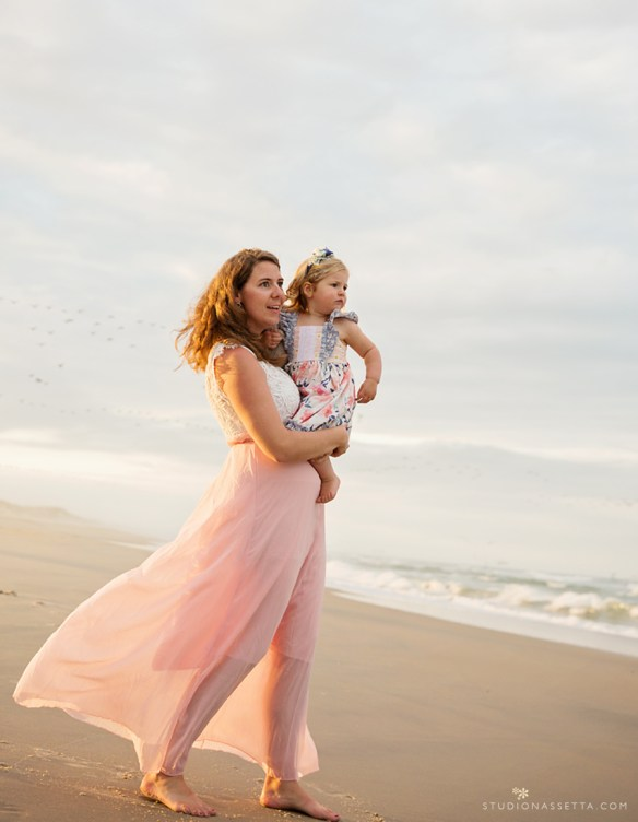 Photo of Mother in flowy dress carrying her daughter by the ocean in the Outer Banks