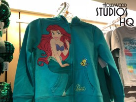 Young Park guests will delight in The Little Mermaid themed apparel and accessories selection. Children's merchandise includes Ariel style dresses, green Little Mermaid front zip jackets, and blue themed caps. Shoppers can select from Mickey Ears complete with fish scale ears and a shell bow highlight, colorful kid's socks, as well as tee shirts inscribed with All Mermaid, All Princess. The Studios Store shelves offer Ariel in a colorful plush along with a photo frame featuring Ariel with her friend Flounder to enhance any favorite photo. Disney's Hollywood Studios. Photo by John Capos
