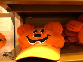 """An array of Disney Halloween themed apparel and other merchandise have bewitched shelves in both Mickey's of Hollywood and Celebrity Five and Dime locations. Shoppers can select from a variety of colorful clothing for any Halloween season activity. Child age trick or treaters have numerous choices for their Disney Halloween style apparel as pictured below. Shoppers can add light up themed accessories for style and night safety that include a Goofy mummy necklace, a Mickey candy pumpkin basket, or even Mickey pumpkin ears. There is also a popular pumpkin light string necklace sure to delight any age. Selections include a Minnie """"Witch Way"""" door mat for the home as well as an attractive Mickey and Minnie Halloween night count down center piece. A Disney pumpkin themed tee shirt awaits adults while women can get in the Halloween spirit with their very own glow in the dark purple tank top. All ages can purchase Mickey or pumpkin design socks to complete that spooky look. Merchandise includes a ghost coffee mug, a character themed candy bowel, as well as Disney character plush decked out in their Halloween costumes. Disney's Hollywood Studios. Photo by John Capos"""