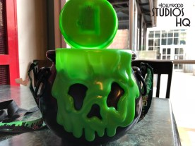 Just in time for the Halloween season, guests can enjoy their hot buttered popcorn in a spooky black cauldron shaped bucket. Complete with a battery operated multi-light flashing green lid with Mickey -faced bubbles on top, this collectable plastic container has a corresponding overflowing green glob Halloween face on the front side as pictured below. The cauldron' backside has Happy Halloween in raised letters just below the overflowing green content. A Disney character themed shoulder strap is included with the characters in Halloween attire. This souvenir cauldron is now available topped off with delicious hot popcorn at various outdoor refreshment booths throughout the park for $15 including tax. After the popcorn is consumed, the container could delight a small child when collecting goodies on their trick or treat outing. Photo by John Capos