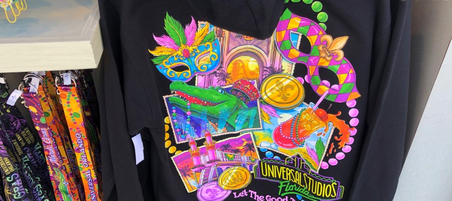 Hollywood Studios HQ provides viewers an exclusive photo preview of popular merchandise for the upcoming 2021 Universal Orlando Mardi Gras International Flavors of Carnaval that begins February 6, 2021. Located in an outdoor kiosk near Mel' s Drive-In in Hollywood, guests have an early shopping opportunity to purchase themed merchandise. This selection includes festive beads, license plates, lanyards, keychains, masks, and a selection of glassware. Colorful adult themed apparel includes hats, tee shirts, and sweatshirts. Stay connected to Hollywood Studios HQ for extensive coverage of this year's exciting Mari Gras. Universal Orlando. Photo by John Capos