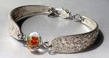 Kim Vredenburg, Floral Fantasies, Vintage silver-plated flatware was formed into a bracelet. The soft glass bead has encased flowers.