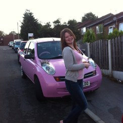 Photograph of Liz in front of a pink car