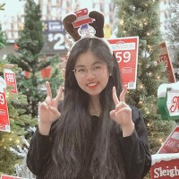 Karen Chu posting in front of Christmas trees with a reindeer antler headband