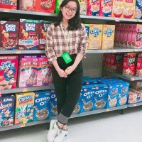 Pham Anh standing in front of a wall with boxes of cereal at the supermarket
