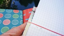 Connect two notebooks with a rubber band., so that the rubber rests on the crease in the middle of each booklet.