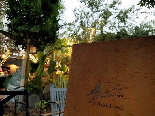 Outdoor seating with rescued bird aviaries at The Perch Brewery
