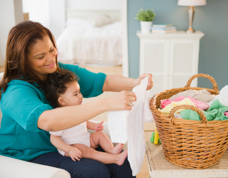 mother folding laundry and holding baby